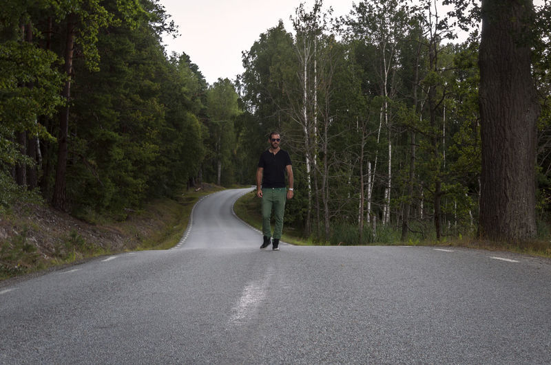 Mid adult man walking on road in forest