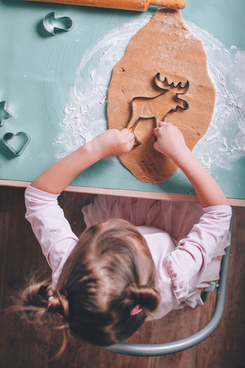 Directly above shot of girl making gingerbread cookie on table