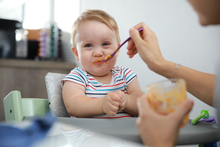 Cropped hand of parent feeding toddler son at home