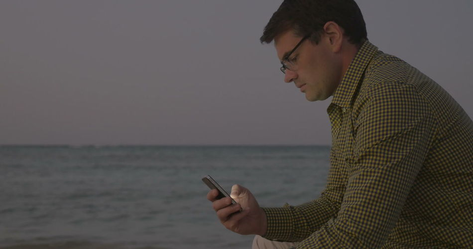 Young man using mobile phone against sea