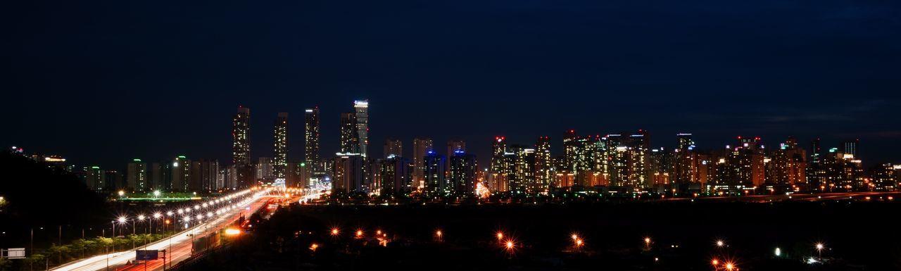 Panoramic View Of Illuminated City Skyline At Night