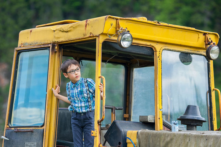 Boy looking away while standing in construction vehicle