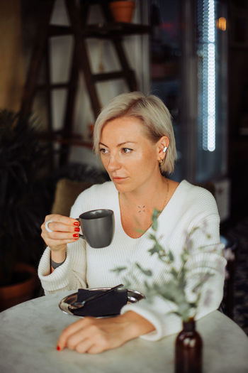 Woman holding coffee cup in restaurant