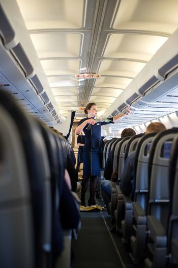 Riga, Latvia - April 03, 2019: Stewardesses in the cabin of the passenger airplane instructs passengers on safety measures in the event of an emergency before the flight from Riga (RIX) to Zurich (Kloten) (ZRH) Flight Stewardess Safety Attendant Airline Airplane Crew Plane Airport Board Latvia Service Aircraft Fly Demonstration Inside Hostess Aeroplane Cabin Aviation Briefing Business Class Commercial Corridor Interior Destination Economy Woman Indoor Instructions Jacket Jet Seats Passengers Journey Transportation Pre-Flight Rescue Seat Ticket Travel Transport People Tourist Tourism Young Adult Lifestyle Color