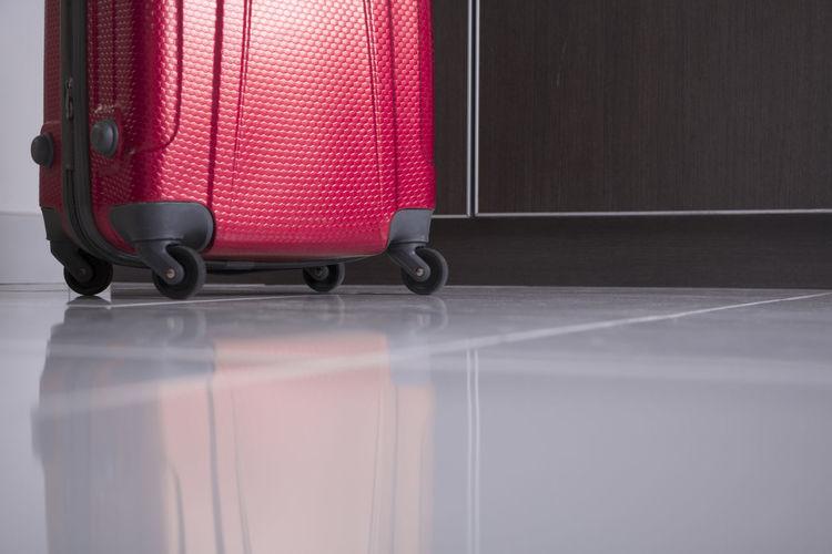 Surface level shot of red wheeled luggage on tiled floor