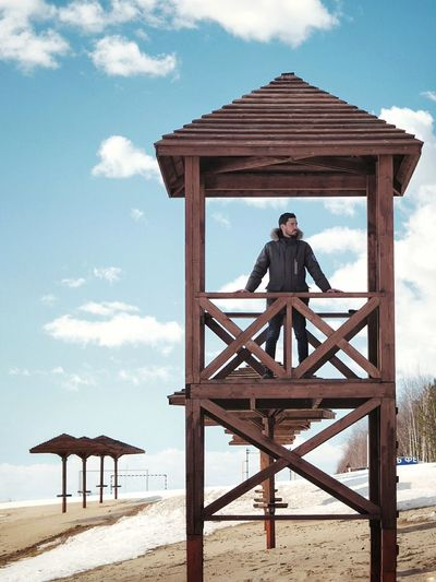 Man Standing In Lifeguard Hut At Beach