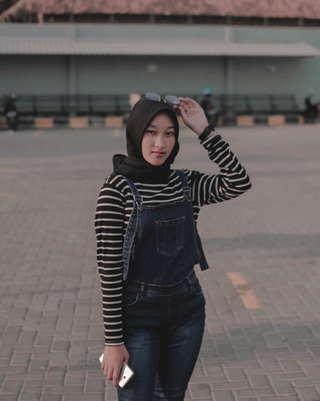 Portrait of teenage girl standing on footpath