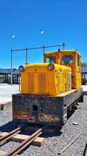 Yellow locomotive against clear blue sky