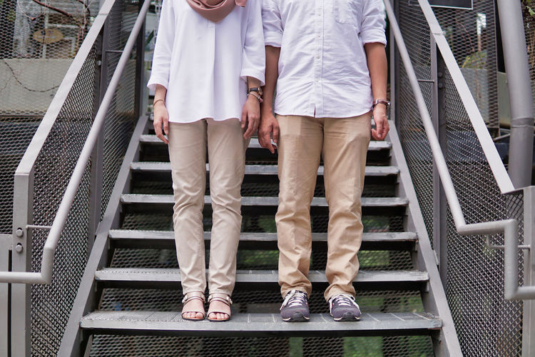 Low section of couple standing on stairs