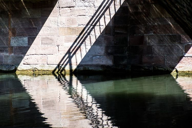 Shadow Shadows & Lights Reflection Water Architecture Built Structure No People Waterfront Day River Bridge Sunlight Bridge - Man Made Structure Wall - Building Feature Building Exterior Underneath Tranquility Outdoors Building 17.62° The Minimalist - 2019 EyeEm Awards