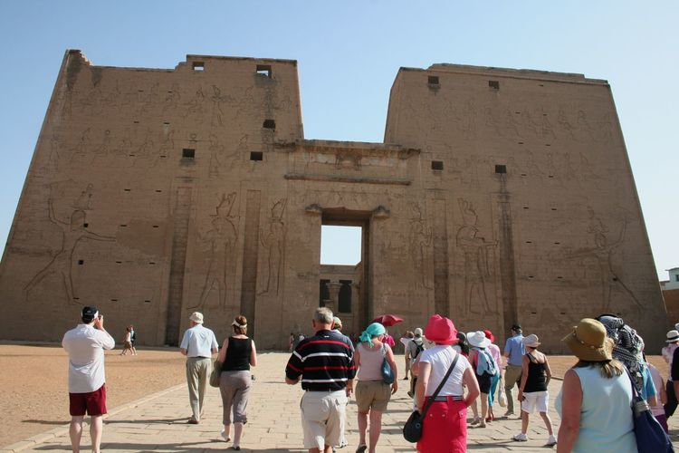 Tourists visiting temple of edfu against clear sky