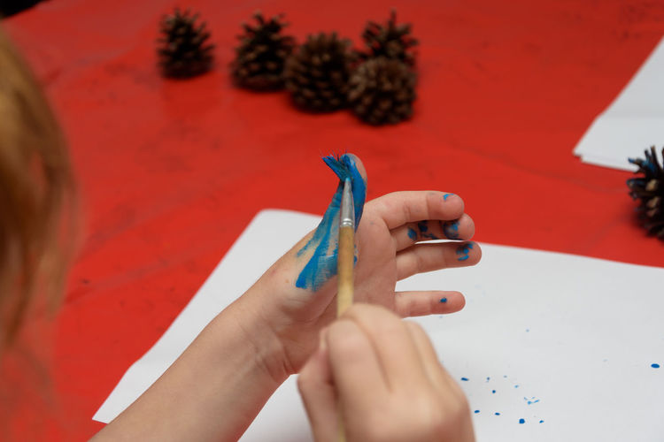 Cropped image of girl painting finger