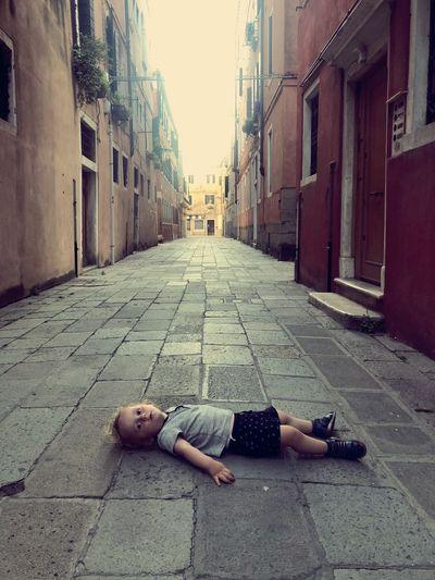 Full length of woman sleeping on street in city