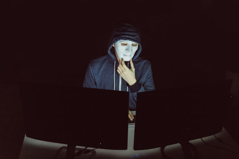 High angle view of hacker hacking using computers at table in darkroom