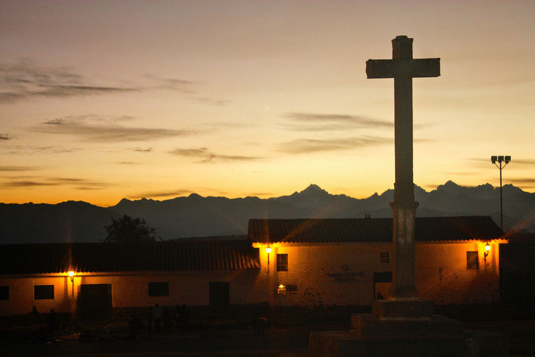 Silhouette cross by building against sky during sunset