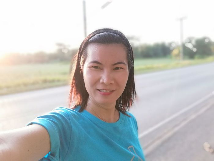 Portrait of smiling mature woman standing on road