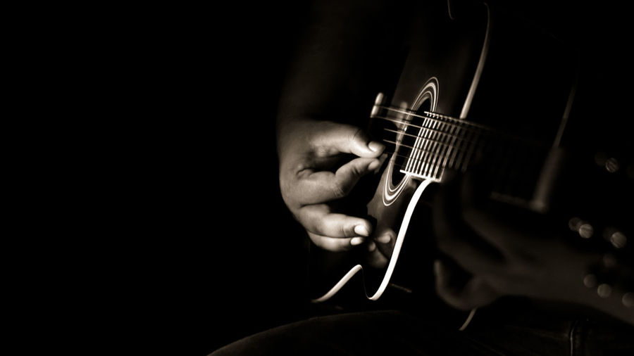 Cropped image of man playing guitar against black background
