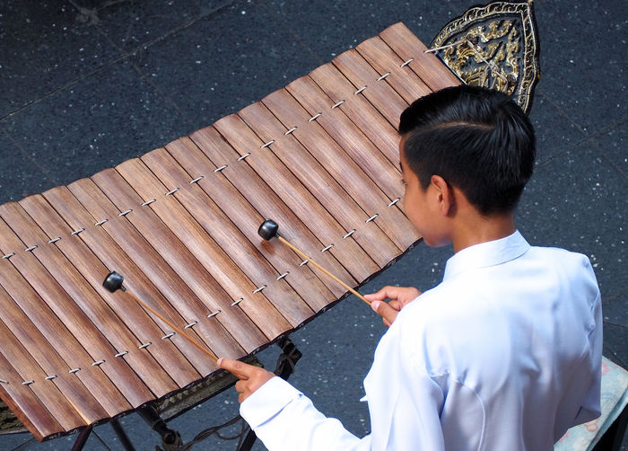 Thai xylophone played by thai people who weared white vintage traditional suit and top view camera. Real People Men Lifestyles One Person Day Leisure Activity Wood - Material High Angle View Outdoors Holding Young Adult Waist Up Rear View Males  Occupation Headshot Standing Casual Clothing Thai Xylophone Played By Thai People Who Weared White Vintage Traditional Suit And Top View Camera. Xylophone; Thai; Instrument; Music; Musical; Thailand; Traditional; Culture; Asian; Performance; Wooden; Classical; Background; Asia; Musician; Percussion; Art; Boy; Education; Playing; Wood; Entertainment; Sound; Oriental; Concert; Performer; Play; Child