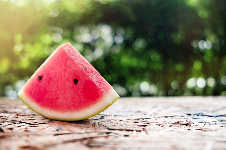 Watermelon Sliced on Wooden Table. Sunlight in Summer as background Fruit Watermelon Selective Focus Healthy Eating Wood - Material Wellbeing Still Life Food Close-up Food And Drink Red Table SLICE Freshness No People Day Outdoors Seed Surface Level Nature Summer Sunlight Sweet