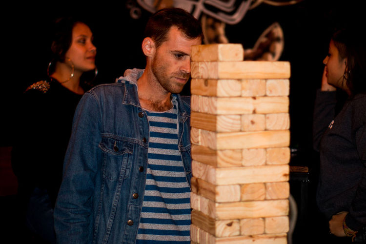 Close-up of block removal game with people in background