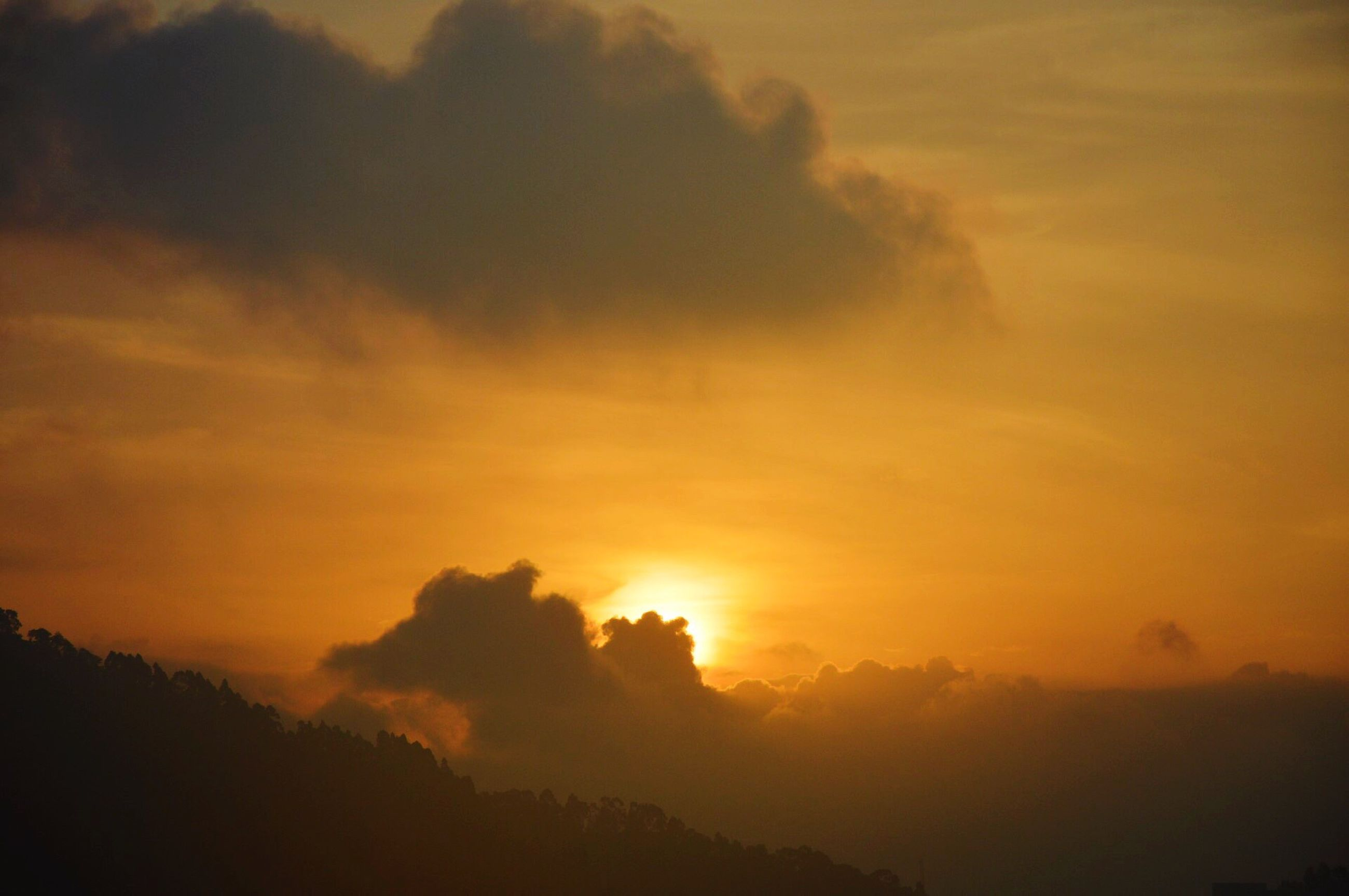 sunset, silhouette, orange color, scenics, beauty in nature, sky, tranquil scene, tranquility, cloud - sky, idyllic, nature, dramatic sky, sun, majestic, cloud, low angle view, outdoors, no people, sunlight, moody sky