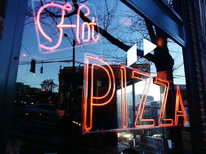 Close-up Of Neon Sign For Hot Pizza At Sunset