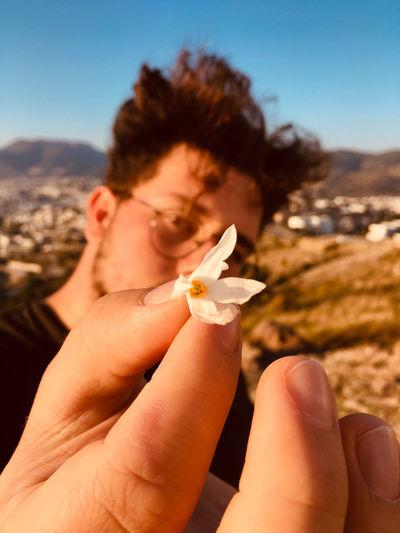 Close-up portrait of man holding flower