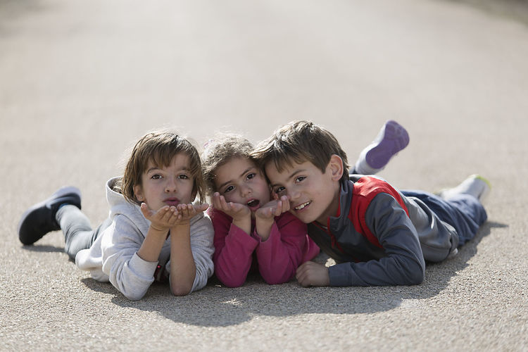Three children lying on the floor one on top of the other. Horizontal shot with natural light Children Children's Portraits Spanish Tree Children Boys Caucasian Ethnicity Child Childhood Day Leisure Activity Looking At Camera Looking At The Camera Lying Down Lying On Front Outdoors People person Portrait Real People Sibling Smiling Togetherness