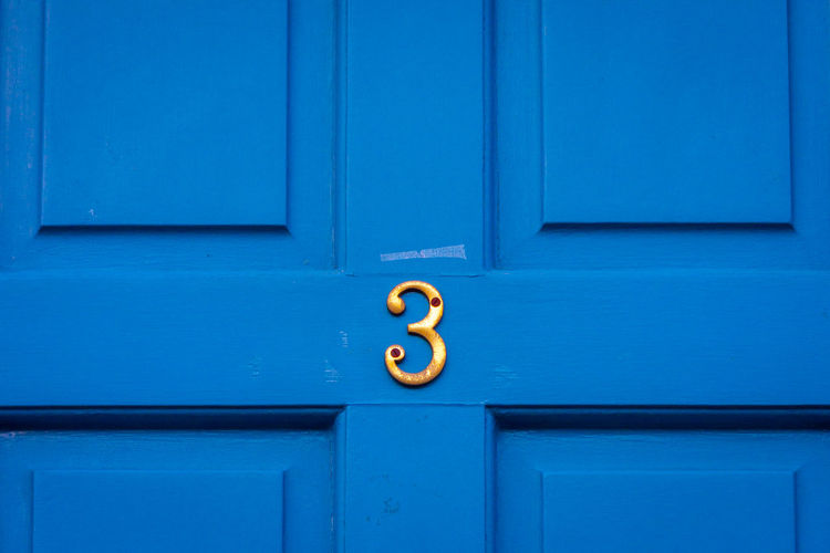 House number 3 on a blue wooden front door