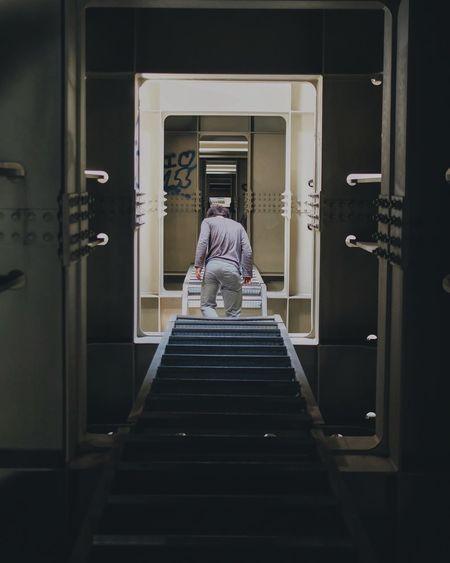 Rear View Of Man Walking In Ship Corridor