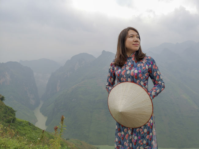 Young Vietnamese women facing and pose for camera with stunning view of the Nho Que river surrounded by mountains from the Ma Pi Leng pass in northern Vietnam Mountain Cloudy Green Color Meo Vac Vietnam Vietnamese Adult Ao Dai Beauty In Nature Casual Clothing Cloud - Sky Day Hairstyle Landscape Leisure Activity Lifestyles Mountain Mountain Range Nature Non-urban Scene One Person Outdoors People Pose Real People Scenics - Nature Sky Standing Sunrise Traditional Dress Tranquility Valley Women Young Women