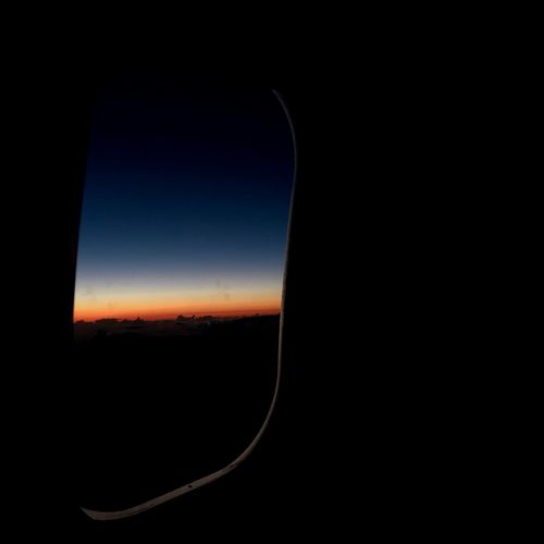 Silhouette landscape against sky during sunset seen through airplane window