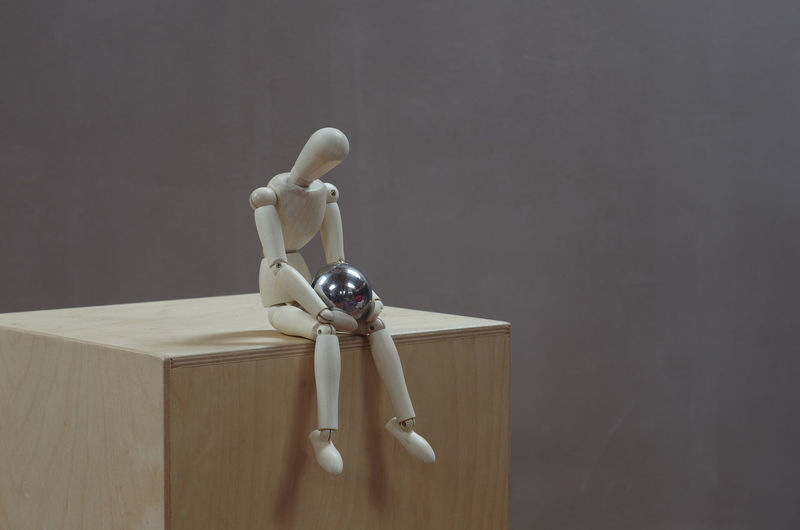 3/4 View Isolated Man Mannequin Pensive Sitting Sphere Thinking Wood Conceptual, Curiosity Dummy Grey Background Horizontal Photo Human Body Part Room For Text Sitting, Seated Steel Ball Wooden Box Wooden Dummy