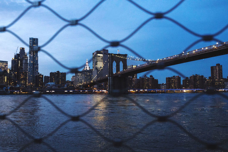 Illuminated city by river against sky seen through chainlink fence