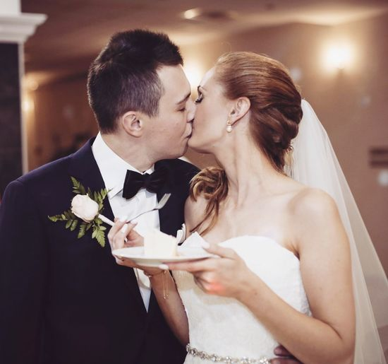 Bridal couple kissing while standing in wedding ceremony