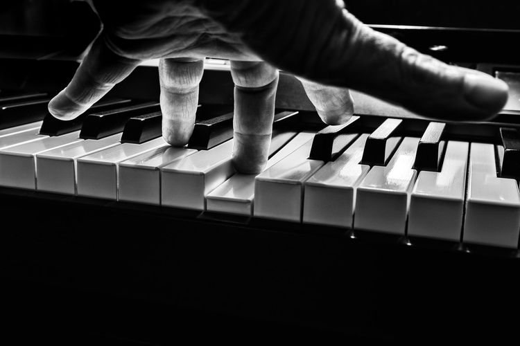 Close-up of person playing piano over black background
