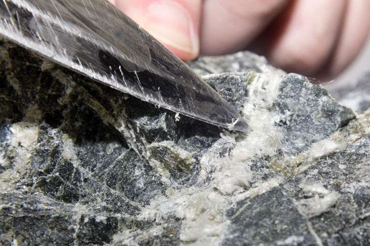 The blade of the knife picks and pulls out the asbestos fibers from the stone.