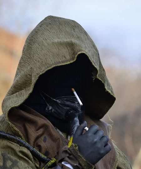 Person wearing costume while holding cigarette and lighter