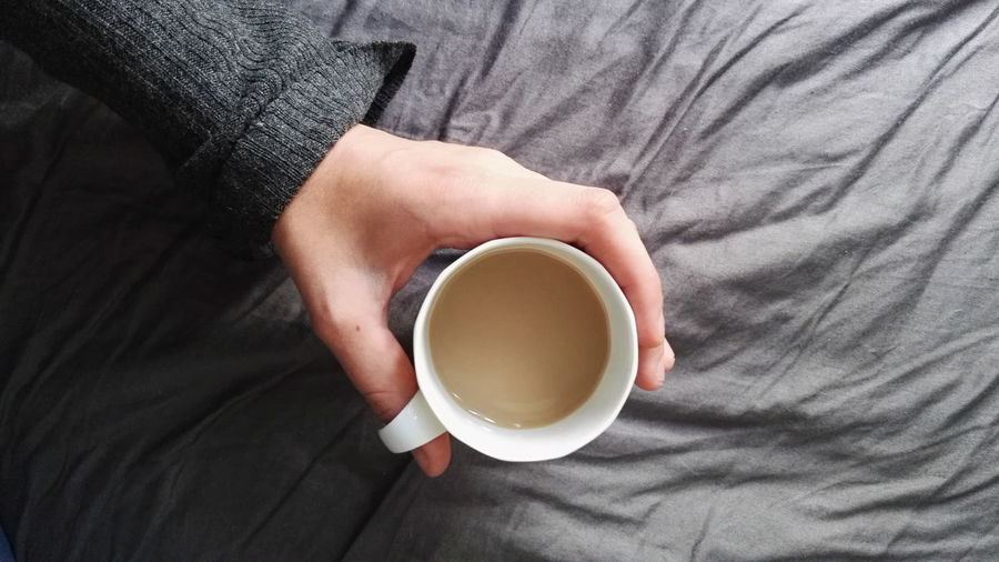 Cropped Image Of Person Holding Coffee On Bed