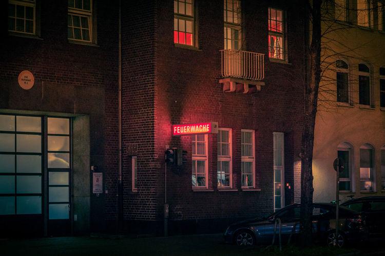 Illuminated street light against building in city at night