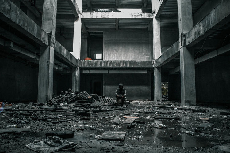 Man sitting in abandoned building