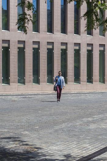 Full length of man walking against building in city