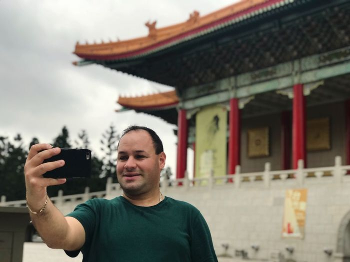 Man taking selfie through mobile phone while standing against temple