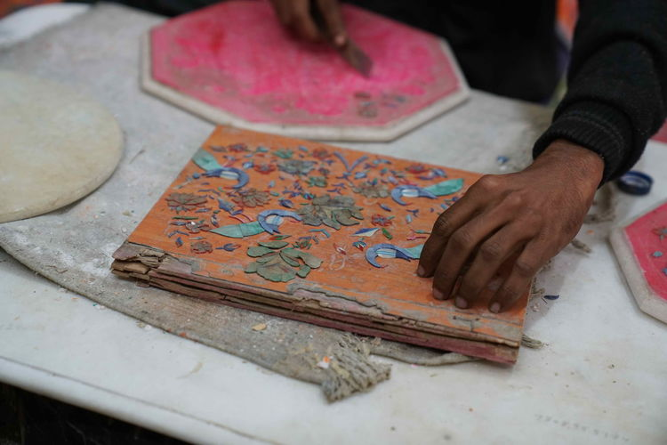 Persian handcraft in Agra Art And Craft Close-up Craft Creativity Day Flower Hand High Angle View Holding Human Body Part Human Hand Indoors  Leisure Activity Men One Person Paper Real People Selective Focus Skill  Table