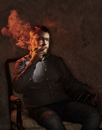 Mature Man Looking Away While Smoking On Chair In Darkroom At Home