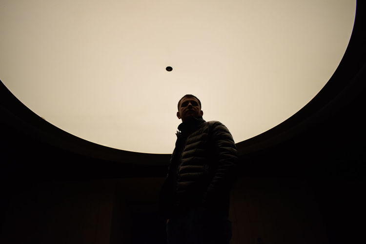 Low Angle View Of Young Man Standing Under White Dome Ceiling In Darkroom