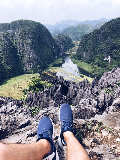 Cliff Edge Of The World Tranquility Hike Travel Destinations Vietnam Ninh Bình High Angle View Top View Mountain Human Body Part Real People Body Part Low Section Personal Perspective Lifestyles Human Leg Shoe One Person Nature Leisure Activity Tree Day Scenics - Nature Mountain Water Land Sky