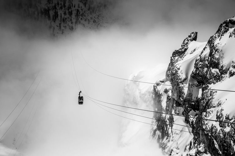 Overhead cable car by snowcapped mountain