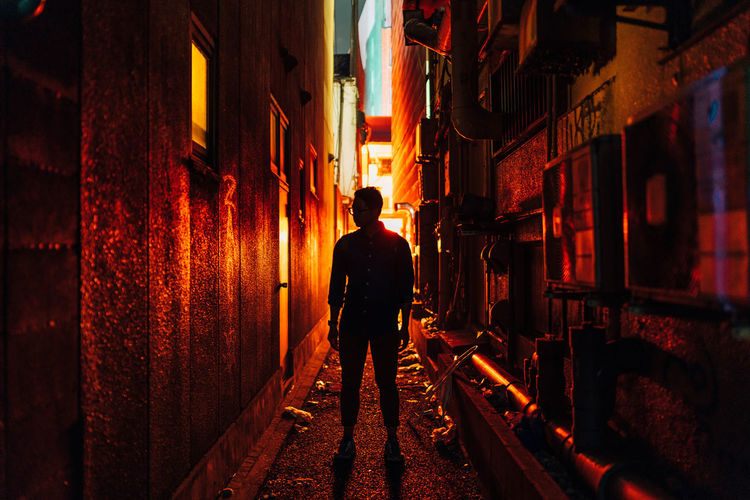 Full Length Of Man Standing In Alley Amidst Buildings At Night