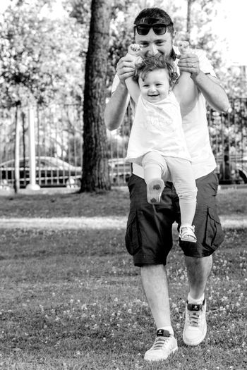 Smiling man playing with daughter in park